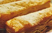 Puff pastry cakes with sugar powder close up