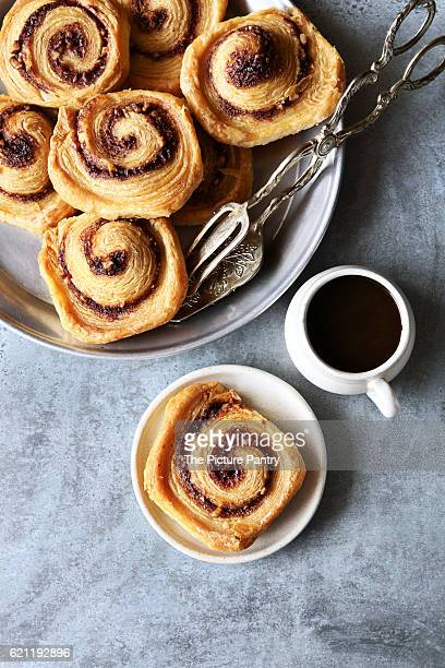 Puff pastry cinnamon rolls on tray with a cup of coffee.Top view