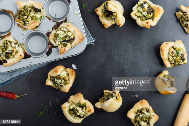 Puff pastry mini tarts with feta cheese and spinach, , top view with copy space for recipe