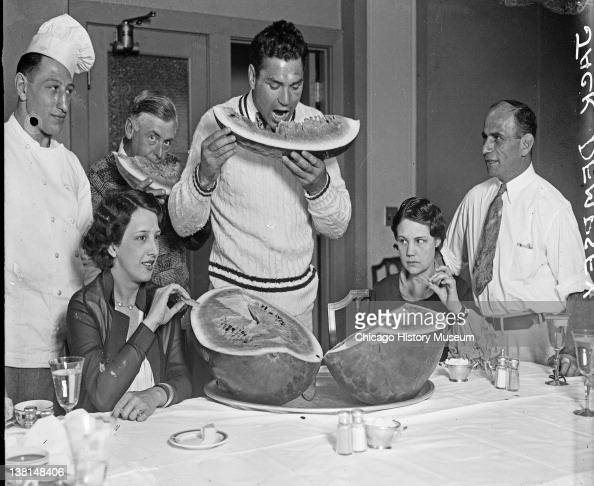 Pugilist Jack Dempsey holding a large halfeaten slice of watermelon to his mouth standing at a dining table with Mrs Jack Dempsey and unidentified...