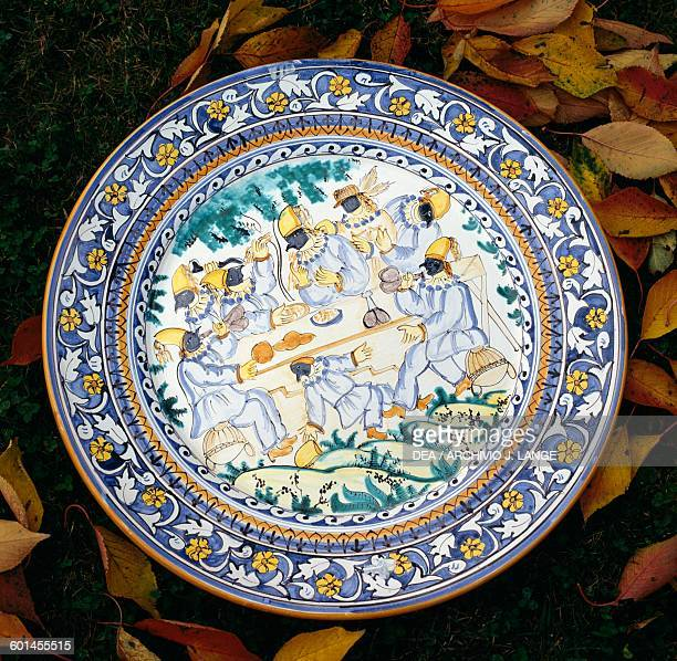 Pulcinellas depicted around a dining table decoration on a majolica plate Benevento Campania Italy