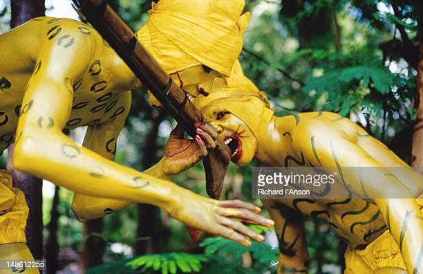Pulikkali (tiger dance) performers ravage hunters gun at Onam festival celebration.