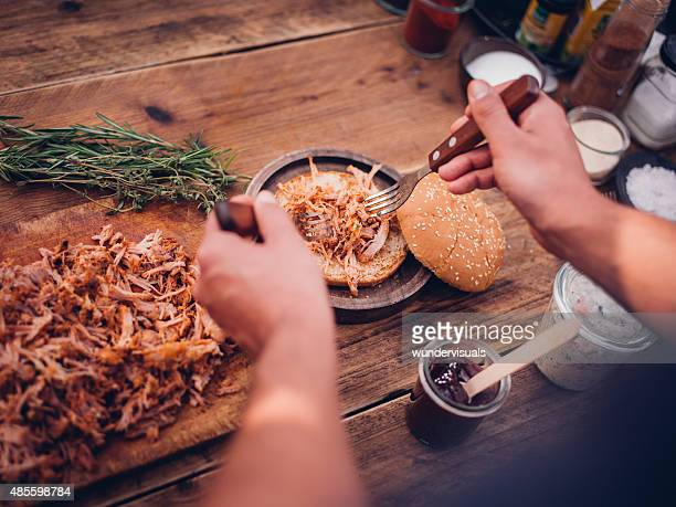 Pulled pork being placed on a burger bun
