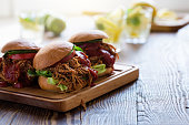 Pulled pork sandwiches with leaf vegetables, tomato on wooden board on picnic table