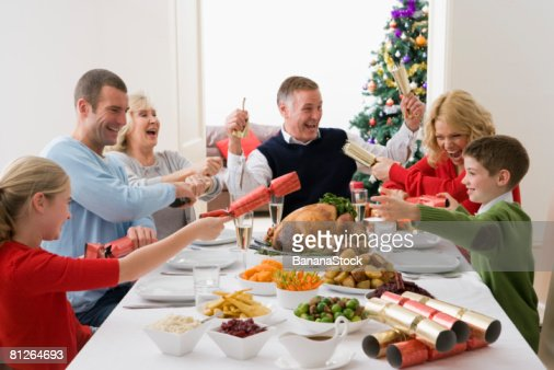 Pulling Christmas crackers at Christmas dinner : Stock Photo