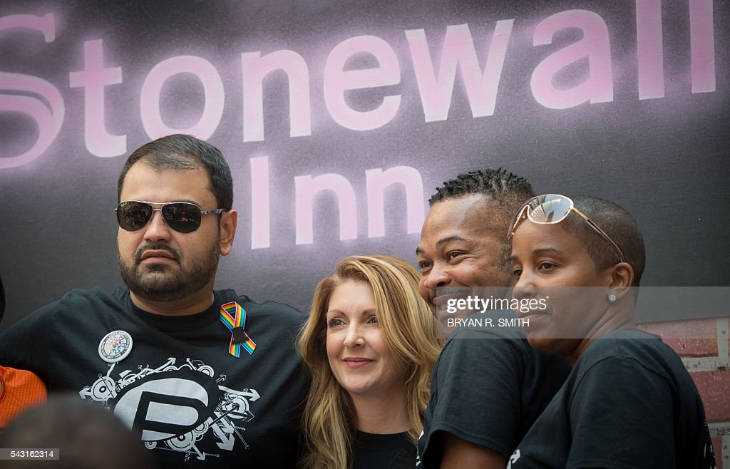 Pulse nightclub owner Barbara Poma, (2nd-L) with the club's entertainment manager Neema Bahrami(2nd-R) pose for a photograph while riding a float during the 46th annual Gay Pride march June 26, 2016 in New York. New York kicked off June 26 what organizers hope will be the city's largest ever Gay Pride march, honoring the 49 people killed in the Orlando nightclub massacre and celebrate tolerance. / AFP / the 46th / Bryan R. Smith