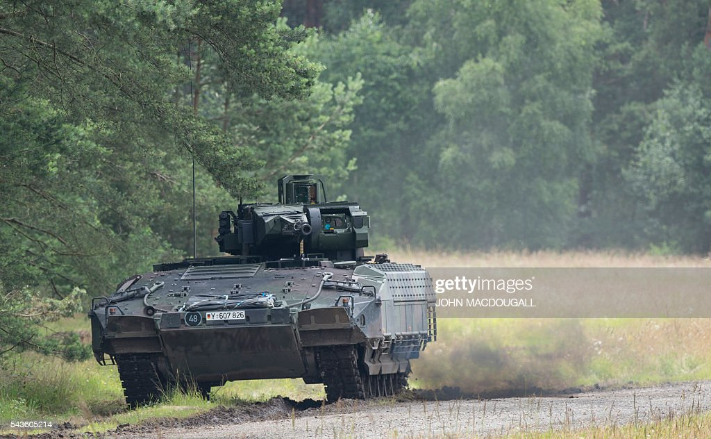 A Puma armoured infantry fighting vehicle heads through a clearing after a simulated ambush during a drill at the headquarters of the 33rd Panzergrenadier bataillon in Neustadt am Ruebenberge on June 29, 2016. / AFP / JOHN