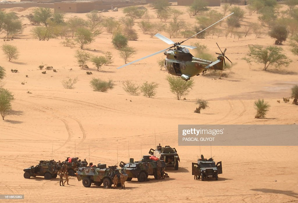 A Puma helicopter flies above French military vehicles on February 17, 2013, near Bourem, northern Mali. A French-led military intervention launched on January 11 has driven the Islamist rebels in Mali from the towns they controlled, but concerns remain over stability amid suicide attacks and guerrilla fighting. AFP PHOTO /POOL / PASCAL GUYOT