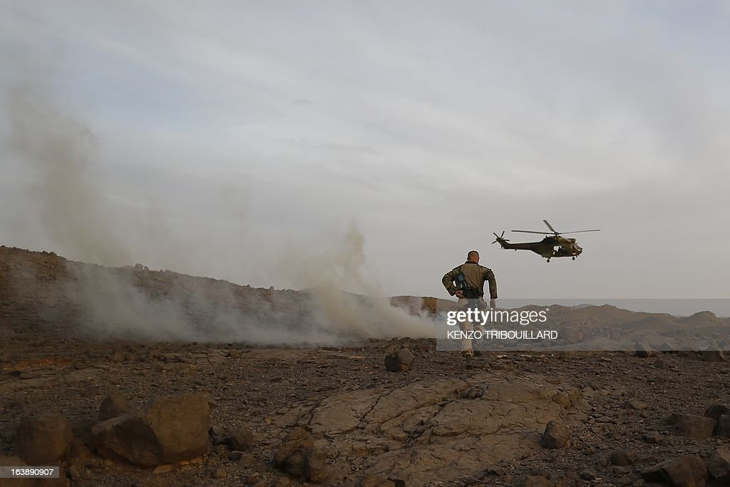 A Puma helicopter lands near a legionnaire of the French army's 2nd Foreign Parachute Regiment in the Adrar of the Ifoghas mountains on March 17, 2013. A French corporal was killed tracking down jihadist fighters in their northern Mali mountain bastions, bringing to five the number of French deaths since Paris launched a military offensive in the country two months ago. Defence Minister Jean-Yves Le Drian said on March 17, 2013 the 24-year-old soldier was killed and three of his comrades wounded when their vehicle was struck by a roadside bomb blast in the Ifoghas mountains, without saying when it happened.
