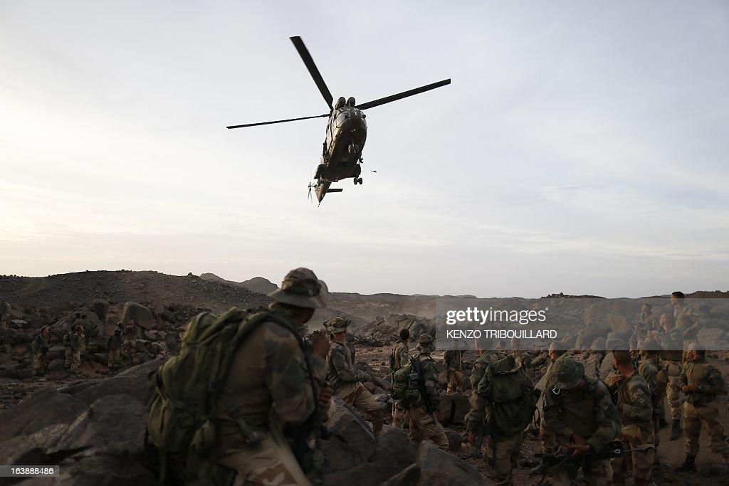 A Puma helicopter lands near legionnaires of the French army's 2nd Foreign Parachute Regiment in the Adrar of the Ifoghas mountains on March 17, 2013. A French corporal was killed tracking down jihadist fighters in their northern Mali mountain bastions, bringing to five the number of French deaths since Paris launched a military offensive in the country two months ago. Defence Minister Jean-Yves Le Drian said on March 17, 2013 the 24-year-old soldier was killed and three of his comrades wounded when their vehicle was struck by a roadside bomb blast in the Ifoghas mountains, without saying when it happened. AFP PHOTO / KENZO TRIBOUILLARD