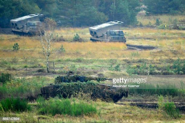 A puma light tank of the Bundeswehr the German armed forces drives by two Mars Rocket Launcher tanks during a simulated attack during military...