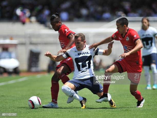 Pumas' Abraham Gonzalez vies for the ball with Lobos Buap's Pedro Aquino and Eduardo Tercero during their Mexican Torneo Apertura 2017 football match...