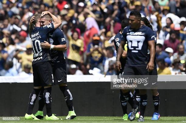 Pumas' forward Nicolas Castillo celebrates with his teammate his goal against America during their Mexican Clausura tournament football match at the...