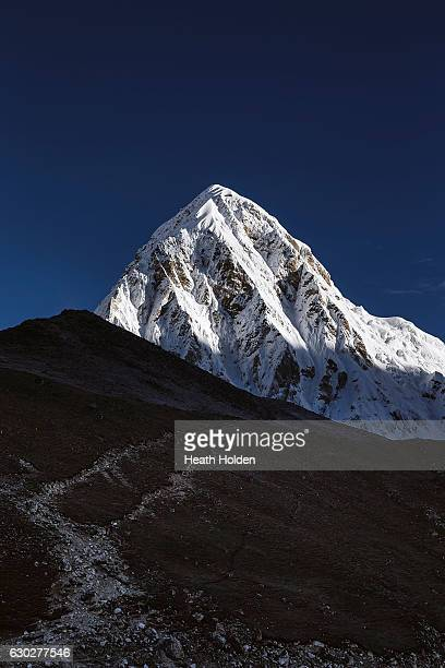 Pumori towers above trekkers climbing Kala Patthar the avalanche which hit Everest base camp during the 2015 earthquake originated on Pumori...