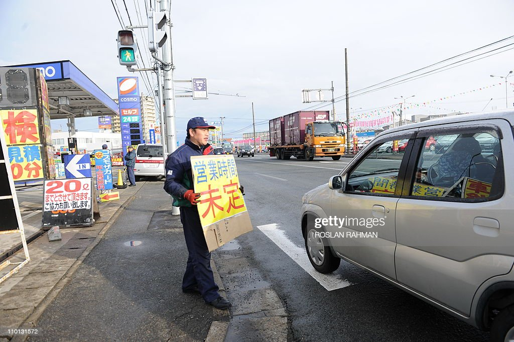 CAPTIONA pump attendant holds a placard telling motorists not to queue up to prevent traffic congestion outside the petrol station in Akita, northwest of Japan on March 16, 2011 as the country rations fuel following the March 11 earthquake and tsunami that devastated the eastern coast of Japan. A fresh fire broke out at a quake-hit Japanese atomic power plant, compounding Japan's nuclear crisis.