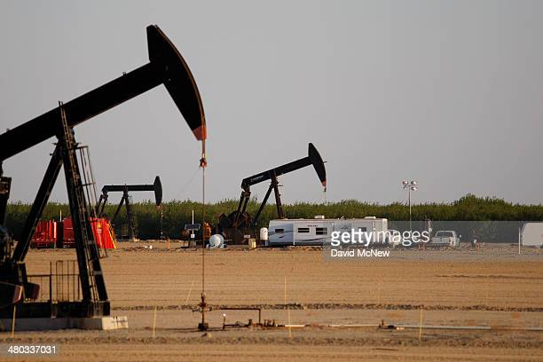 A pump jack and frac tanks stand in field being developed for drilling next to a farm over the Monterey Shale formation where gas and oil extraction...
