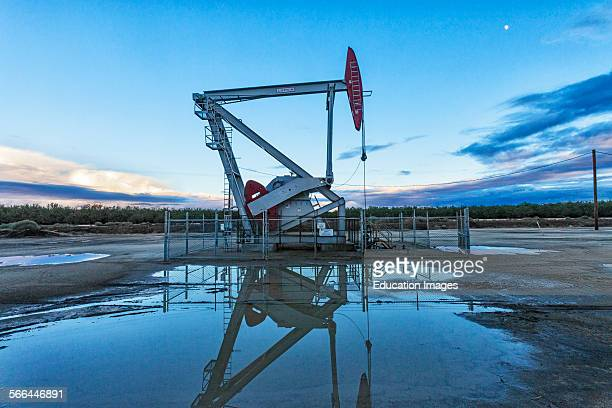 A pump jack and surface water at oil well and fracking site in Shafter Kern County located over the Monterey Shale has seen a dramatic increase in...