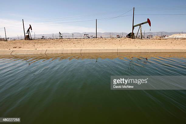 Pump jacks are seen next to a canal in an oil field over the Monterey Shale formation where gas and oil extraction using hydraulic fracturing or...
