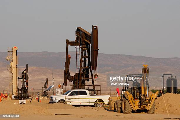 Pump jacks stand in field being developed for drilling next to a farm over the Monterey Shale formation where gas and oil extraction using hydraulic...