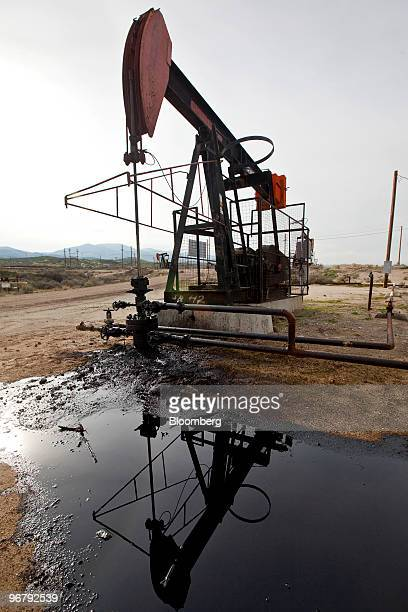 A pumpjack also known as a nodding donkey is reflected in spilled oil above a Chevron Corp oil well in the MidwaySunset oil field near Taft...