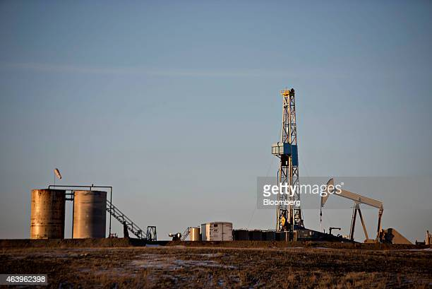 A pumpjack operates in the foreground of a crude oil drilling rig outside Williston North Dakota US on Thursday Feb 12 2015 A plunge in global energy...