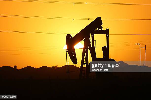 A pumpjack sits on the outskirts of town at dawn in the Permian Basin oil field on January 21 2016 in the oil town of Midland Texas Despite recent...