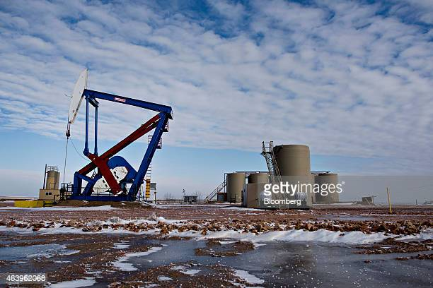 A pumpjack stands near storage containers on the site of an oil well outside Williston North Dakota US on Thursday Feb 12 2015 A plunge in global...