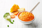 Pumpkin and carrot baby puree in bowl with baby spoon on white wooden table