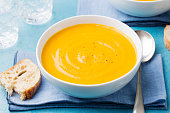 Pumpkin and carrot soup with cream on blue stone background