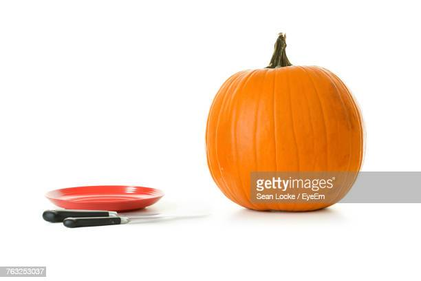 Pumpkin And Plate With Knives Against White Background