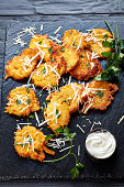 Tasty pumpkin fritters with italian parmesan cheese and sour cream and parsley on a black stone board, vertical