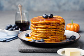Pumpkin pancakes with maple syrup and blueberries on a plate. Grey stone background.