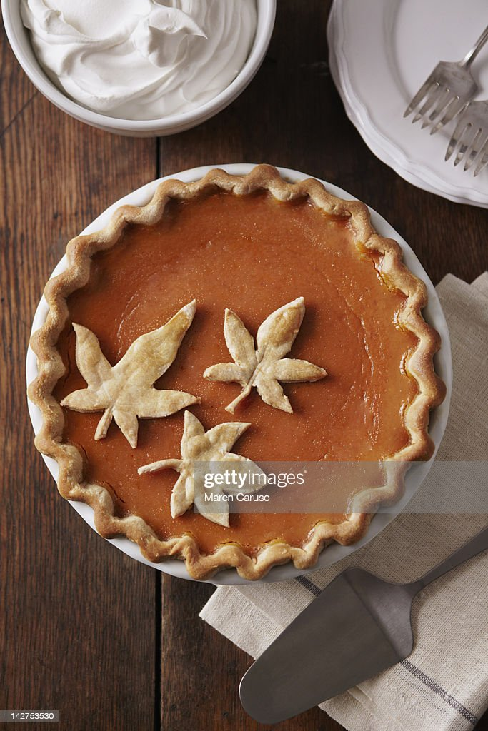 Pumpkin pie with leaf detail on wood table : Stock Photo