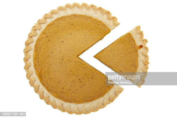 Pumpkin pie with one slice cut out, overhead view