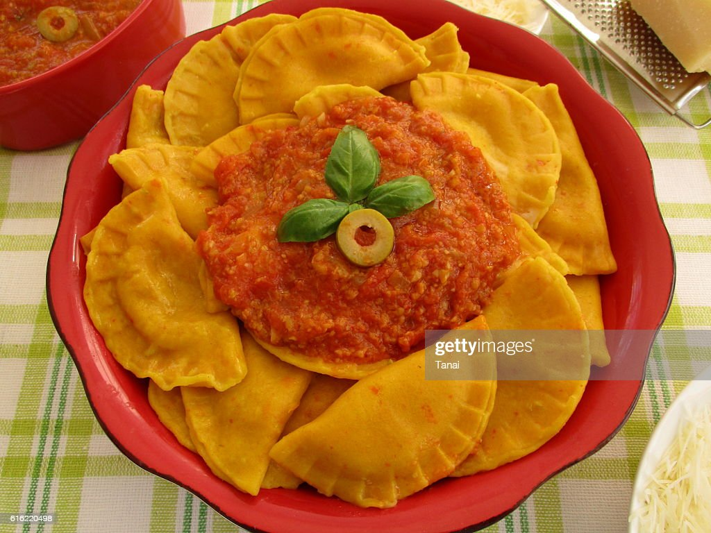 Pumpkin ravioli with tomato and olive sauce in red bowl : Stock-Foto