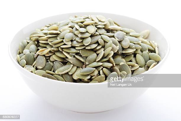 pumpkin seeds in white bowl isolated on white