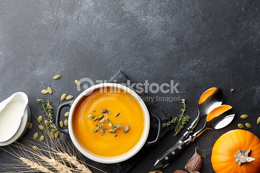 Pumpkin soup with thyme and pumpkin seeds on black background : Stock Photo