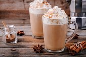 Pumpkin spice latte with whipped cream and cinnamon in glass on wooden background
