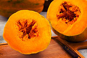 Pumpkin with orange pulp and fibers in the middle, cut with a knife into two parts.