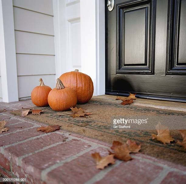 Pumpkins in front of door of house