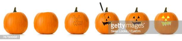 Pumpkins With Anthropomorphic Face Against White Background