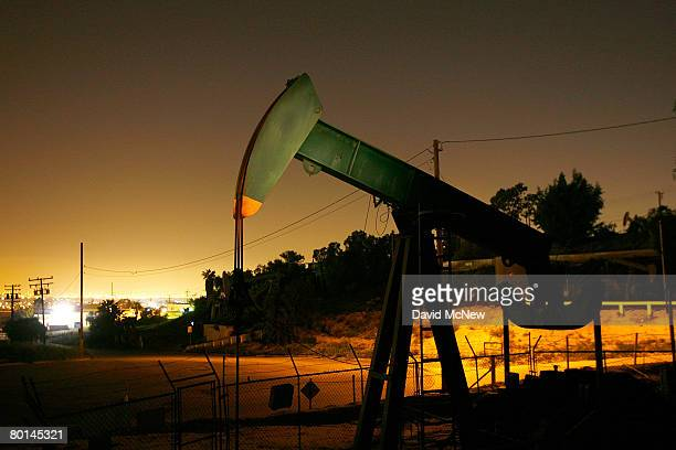 Pumps draw petroleum from oil wells through the night as the cost of crude oil tops $104 per barrel in its surge to new record high prices March 5...
