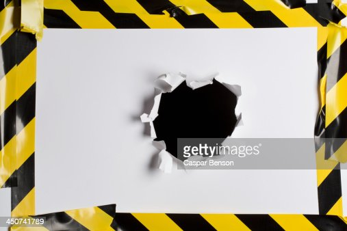 A punched out hole in cardboard with cordon tape around it