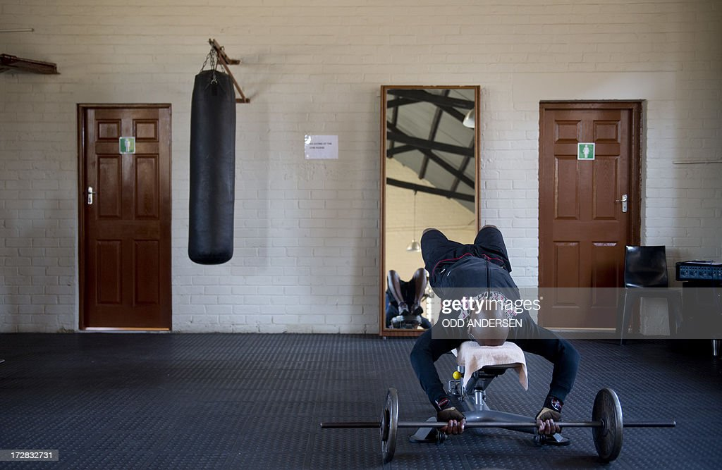 A punching bag hangs next to a man lifting weights in the gym of the Donaldson Orlando Community Centre (aka Soweto YMCA) in the East Orlando, Soweto on July 3, 2013. In a sweaty township gym where former South African President Nelson Mandela once trained as a young boxer, athletes are still pumping iron today, inspired by the peace icon's example as he fights for his life in hospital.