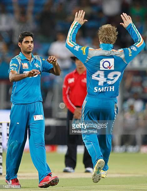 Pune Warriors bowler Bhubneshwar Kumar celebrate with teammate Steven Smith after capturing the wicket of Mumbai Indians batsman Ambati Rayudu during...