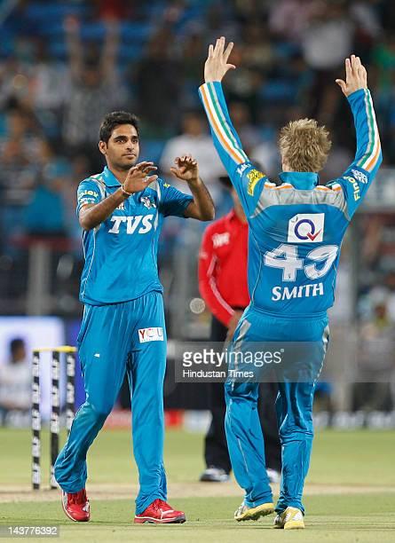 Pune Warriors bowler Bhubneshwar Kumar celebrates with Steven Smith after capturing the wicket of Mumbai Indians batsman Ambati Rayudu during the...