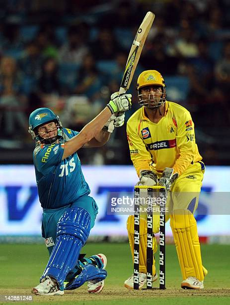 Pune Warriors India batsman Steven Smith watched by Chennai Super Kings cricketer Mahendra Singh Dhoni plays a shot during the IPL Twenty20 cricket...