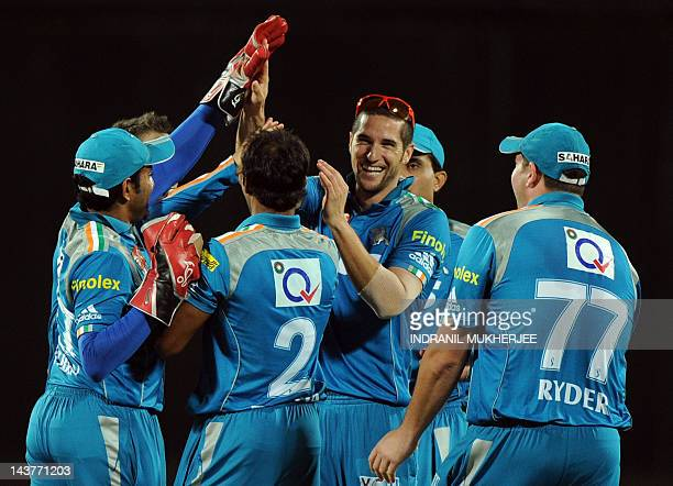Pune Warriors India cricketers greet teammate Wayne Parnell after the dismissal of unseen Mumbai Indians batsman Harbhajan Singh during the IPL...