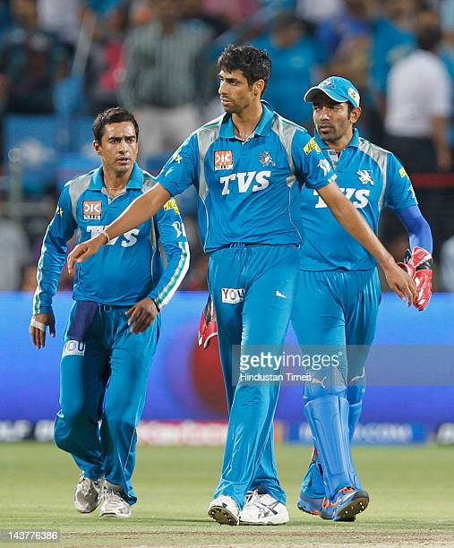 Pune Warriors player Ashish Nehra celebrates with teammates after capturing the wicket of Mumbai Indians batsman Sachin Tendulkar during the Indian...