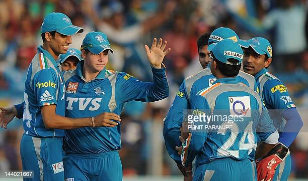 Pune Warrirors India player Steven Smith celebrates with team mate Ashish Nehra and others after taking the wicket of Rajasthan Royals batsman...